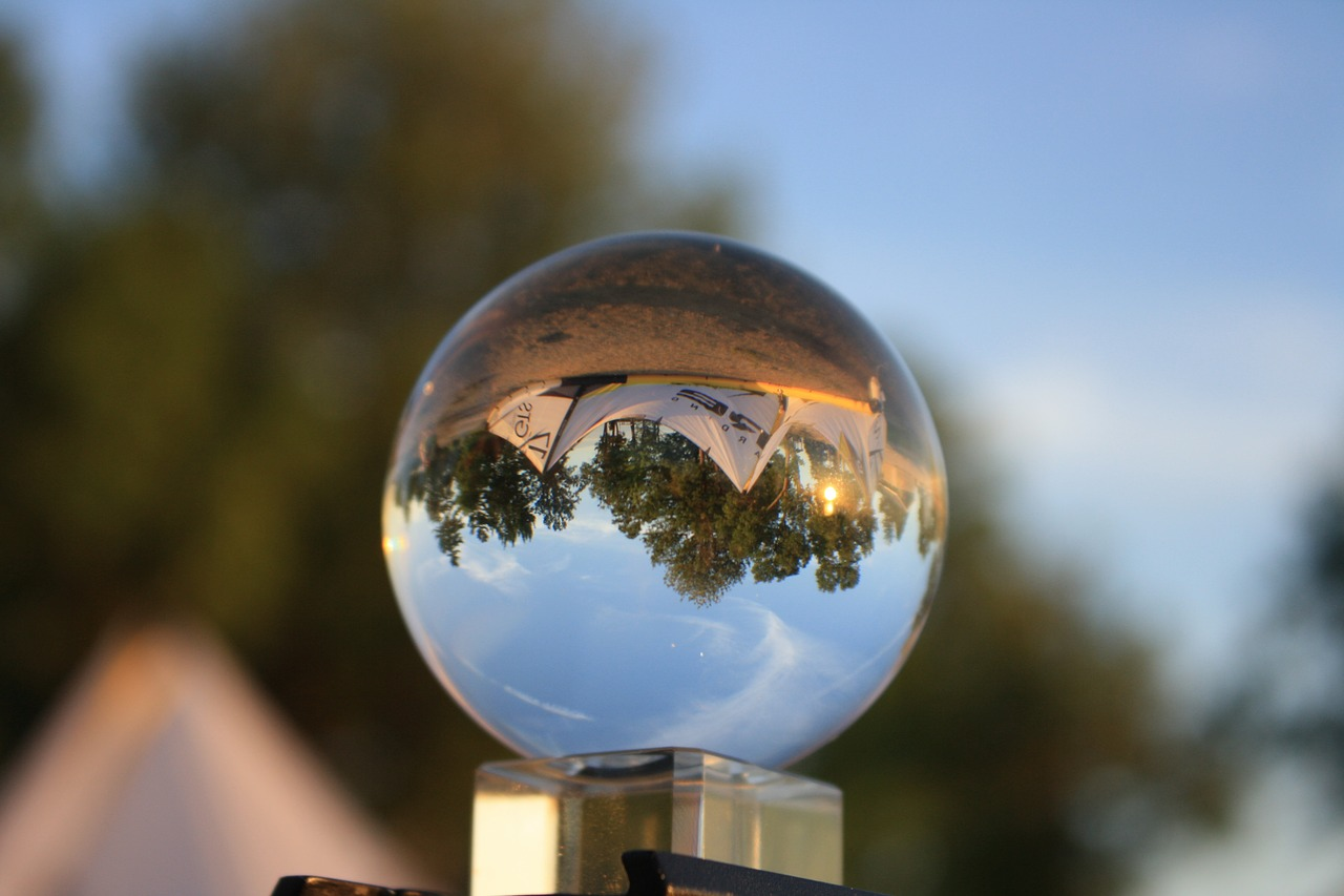 A crystal ball reflecting a cityscape with blue skies in the background