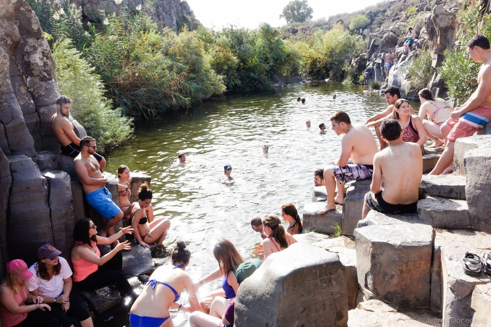 Cooling off in one of the swimming holes along the Yehudiya Canyon Trail, Golan Heights, Israel. This is one of many beautiful swimming holes in the area, flanked by hexagon-shaped basalt columns.