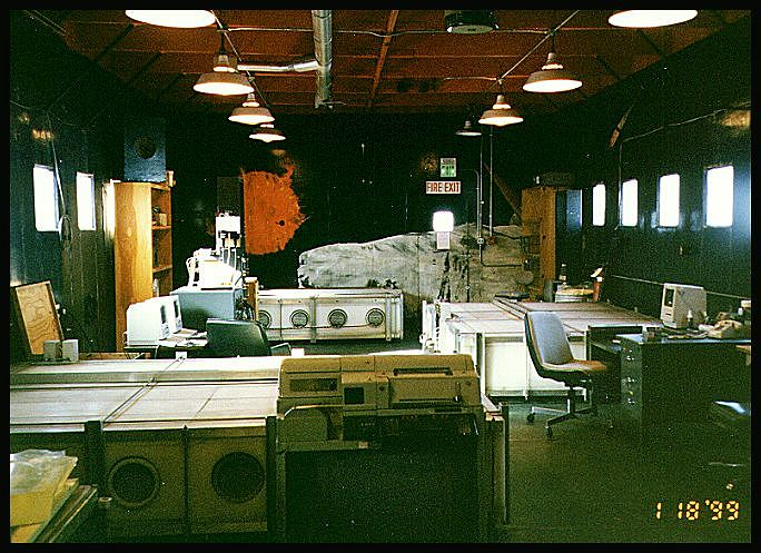 From https://neutronm.bartol.udel.edu/stations/mcmurdo.html : Inside the Cosmic Ray Lab. The neutron monitor is in three sections (white structures on floor) each containing six neutron detector tubes. Photo by L Shulman, 1999.