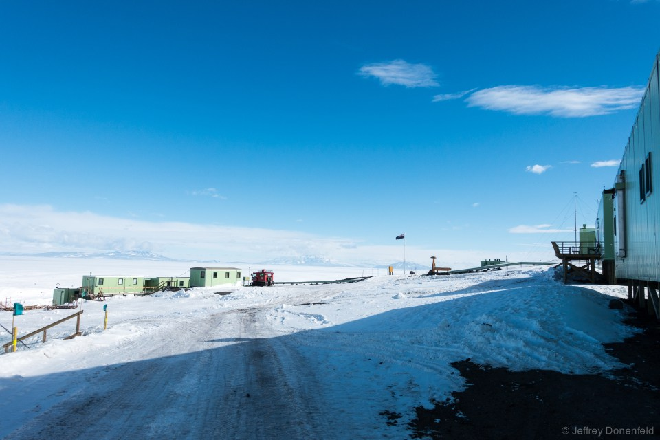 Entering the main quad of Scott Base, the main administration building is on the right, and flagpole/placemarker straight ahead. To the left is the Ross Sea and McMurdo Sound.