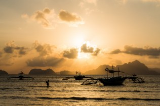 Sunset in El Nido, with outrigger dive boats anchored in the shallows.
