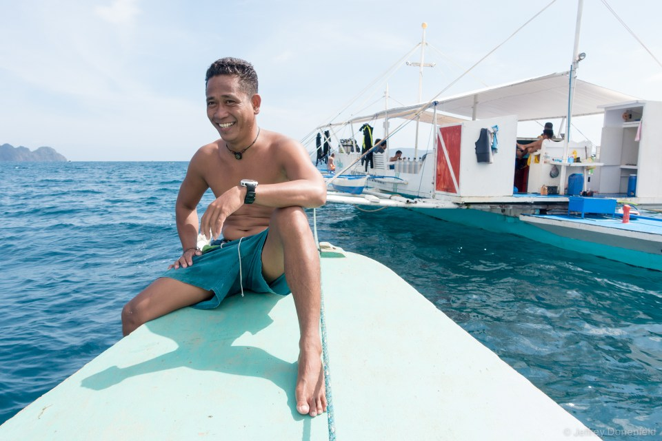 Our divemaster on the bow of the dive boat. Dive boats in the Philippines are typical double-outrigger boats.