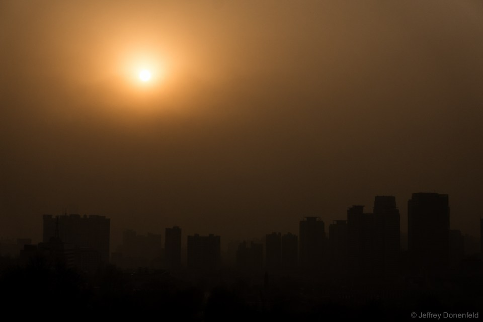 Amongst the sparkling lights, toxic smog, blown in from China, blankets the city and obscures the sunset.
