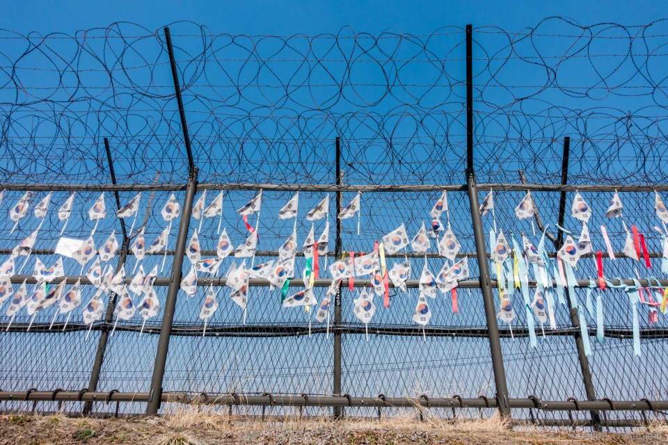 On the Southern side of the DMZ area, a barbed wire fence is coated in South Korean flags, in support of reunification, albeit on South Korea's terms, of course.