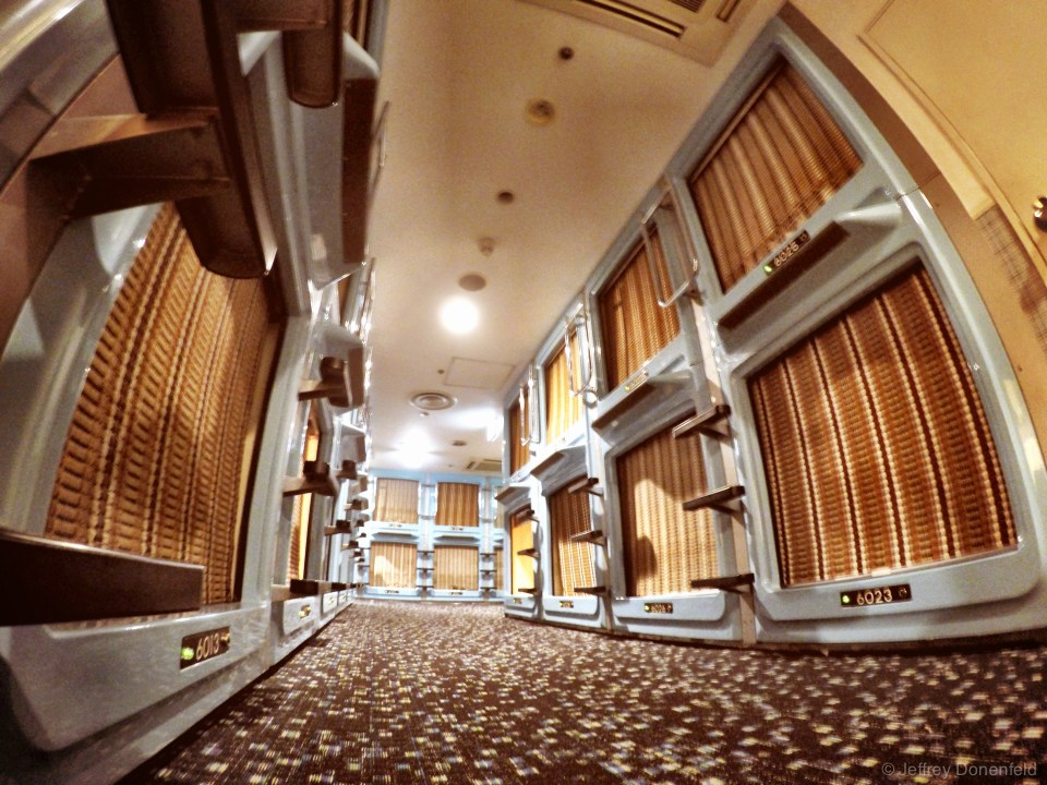The hallway of the Shinjuku Kuyakushomae Capsule Hotel, featuring double-stacked capsules. The entrance to the capsule is covered with a bamboo screen, which blocks light, but not sound, and does not lock. For valuables, you get a secure locker downstairs.