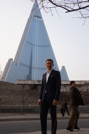 In Pyongyang, I made a stop with my group for lunch at a restaurant right across the street from the giant Ryugyong Hotel. I was scolded for having this picture taken of me, because it shows the shanty village that surrounds the giant uninhabited building.