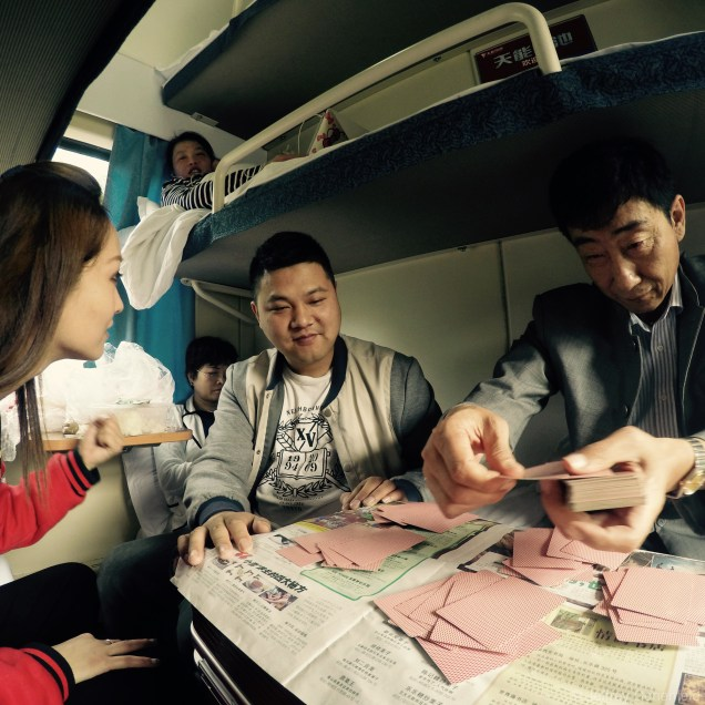 Learning to play Chinese poker with my friends on the train to Hong Kong. This family was traveling to Hong Kong to buy baby formula.