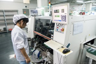 A worker monitors a pick-and-place machine at Seeed Studio. This machine automates the production of circuit boards and other electronics.