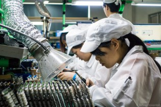 A worker hand-solders a circuit board for a small run of eletronics.