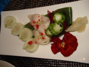 A plate of white tuna arranged as hibiscus flowers.