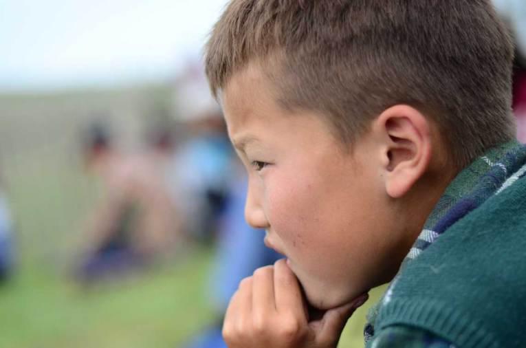 Enfant regardant le match de lutte mongole
