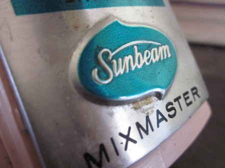 This is a close up of the metal label on the handle of a vintage Sunbeam Mixmaster, a pastel pink hand mixer.