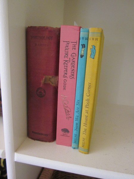 This is a photo of four old books in a white bookcase. The books are PHUNOLOGY, which is burgundy, GARDENERS AND BEEKEEPERS ANNUAL, which is pink, NOW WE ARE SIX which is blue, and THE HOUSE AT POOH CORNER which is yellow.