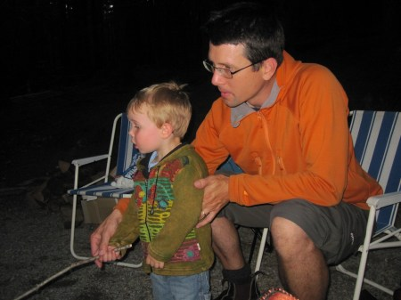 This is a picture of a 3 year old blonde boy roasting a marshmallow under the careful supervision of his dad.