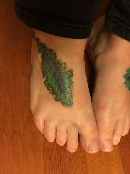 This is a picture of a kale leaf tattooed in a watercolour style on my right foot.