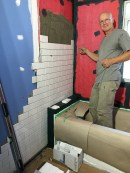 Wall tiles going in - Micah uses a very ingenious method of spacing them with nylon string.