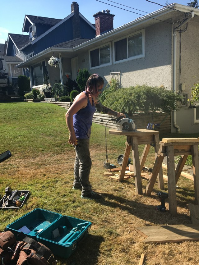 A photo of a tradesperson. She is holding a skilsaw in one hand and sawing a piece of wood clamped to a sawhorse.