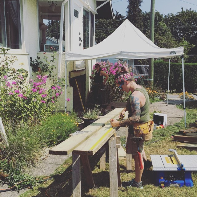 A photo of two tradespeople working on a house. In the foreground, a carpenter measures a stringer to cut. In the background, a carpenter is inspecting a component of the house.