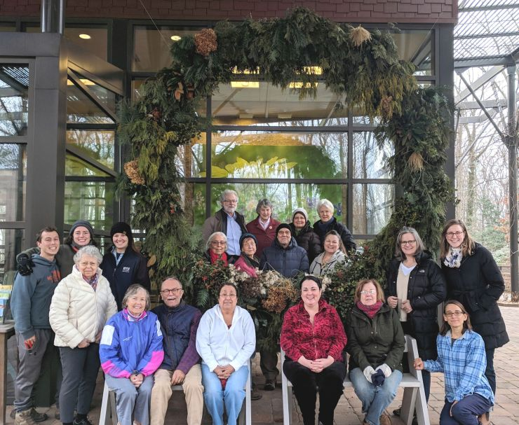 A group of 20 smiling staff members and volunteers standing and sitting in front of a giant holiday wreath. Some are wearing coats and hats, some have arms around each other.