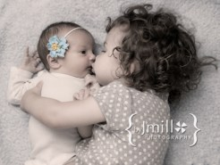 Newborn baby photographed with her older sibling