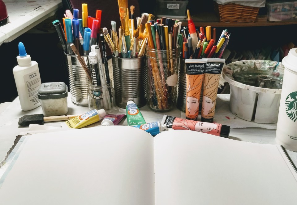 art supplies; art as self care in times of uncertainty. open blank journal, glue, markers, paints, pencils.