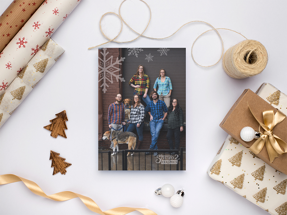 Image of the holiday card on a table with gold holiday wrapping paper, string and tree cut outs
