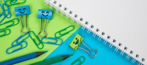 image of a blank piece of paper, green and blue pencils, paper clips and binder clips with smiles drawn on