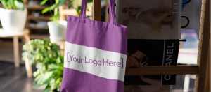 """Image of a purple tote bag hanging on the back of a chair with the text """"your logo here"""""""
