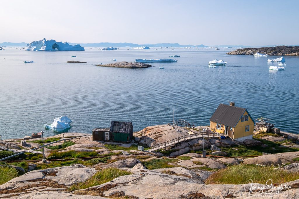 A view over Disko Bay, Ilulissat, Greenland, with a small yellow house perched on the rocks and a huge iceberg with elegant arches in the distance.