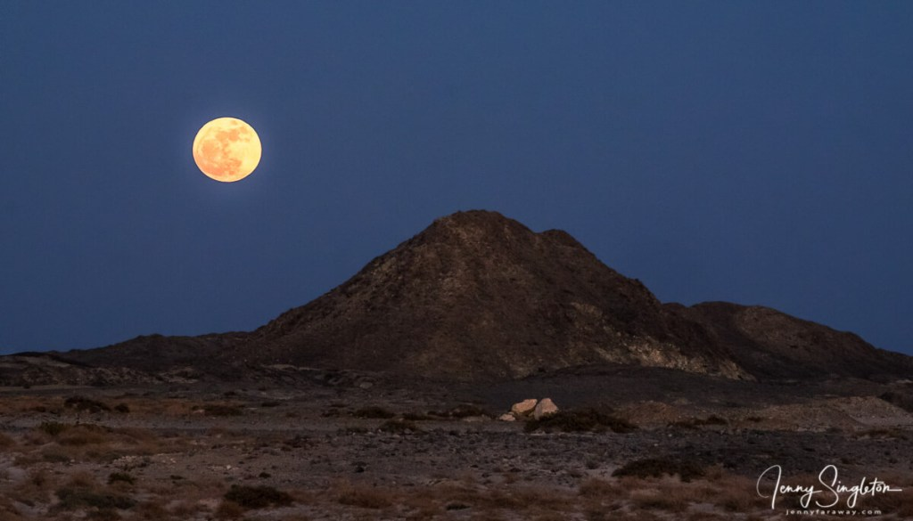 The full moon rises over a hill on Masirah Island, Oman