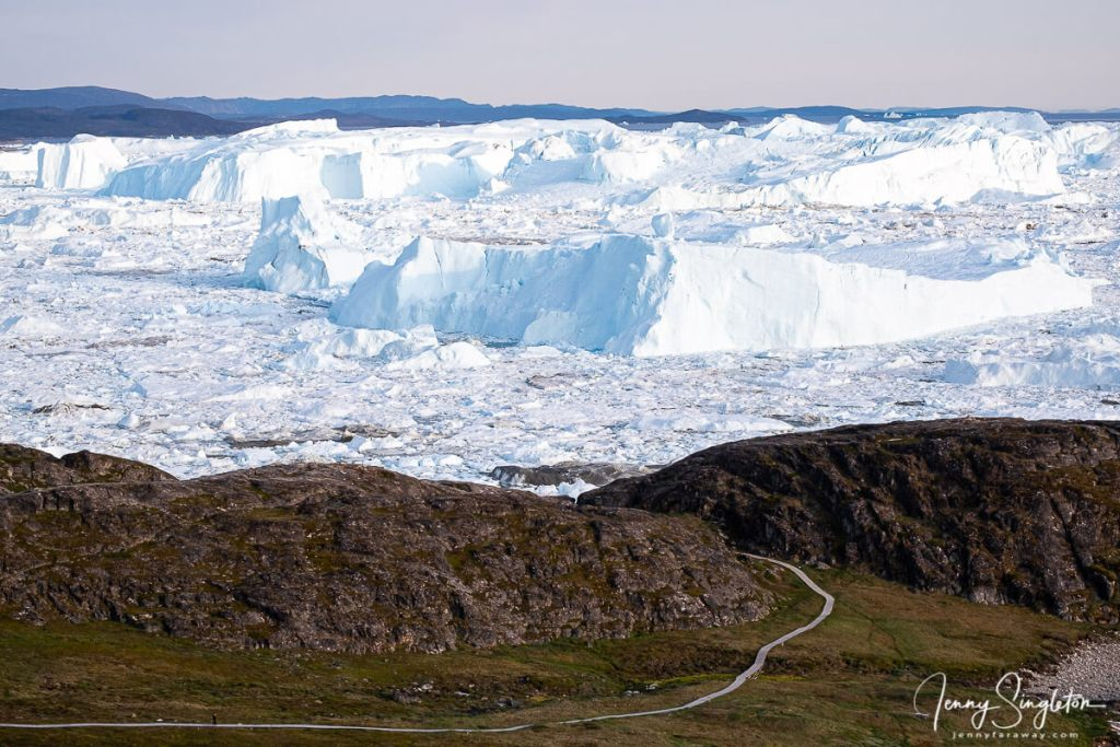 The boardwalk of the Blue Trail winds down to the extensive icebergs of Ilulissat Icefjord, as seen from the Yellow Trail