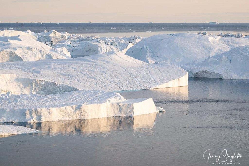 The Icebergs of Ilulissat Icefjord glow yellow under the midnight sun in Greenland