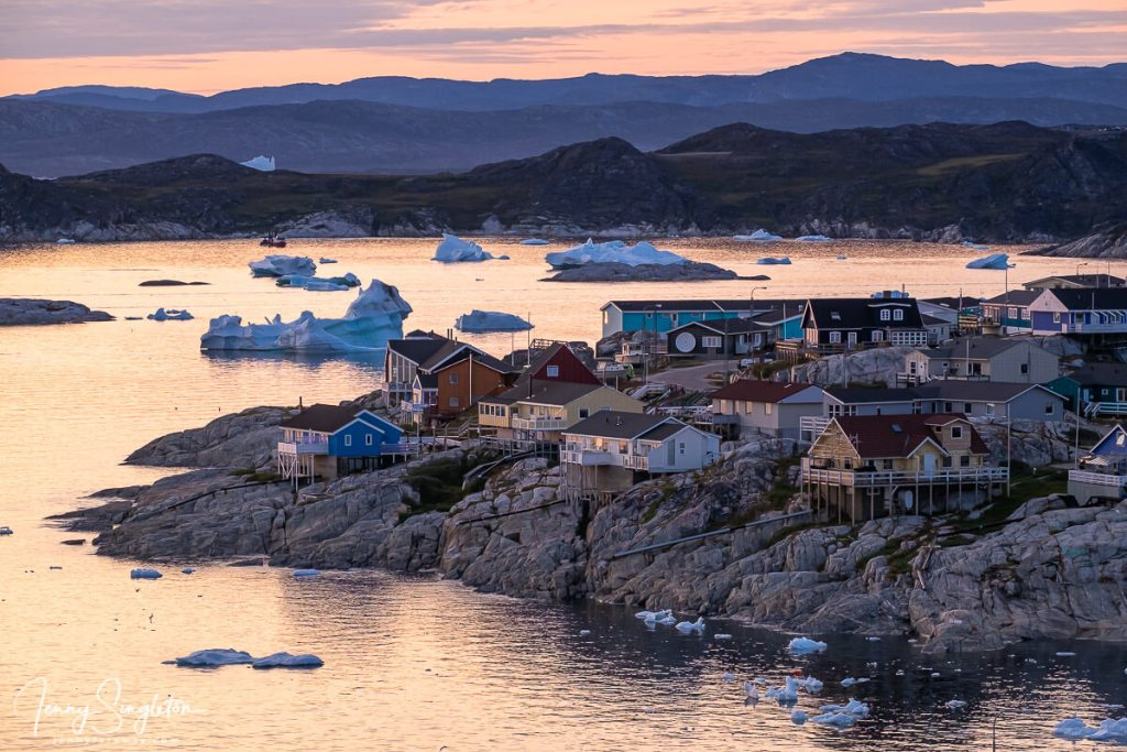 The houses of Ilulissat perch on the rocks overlooking Disko Bay, while the midnight sun provides a pink glow reflected in the water. Icebergs dot the scene.