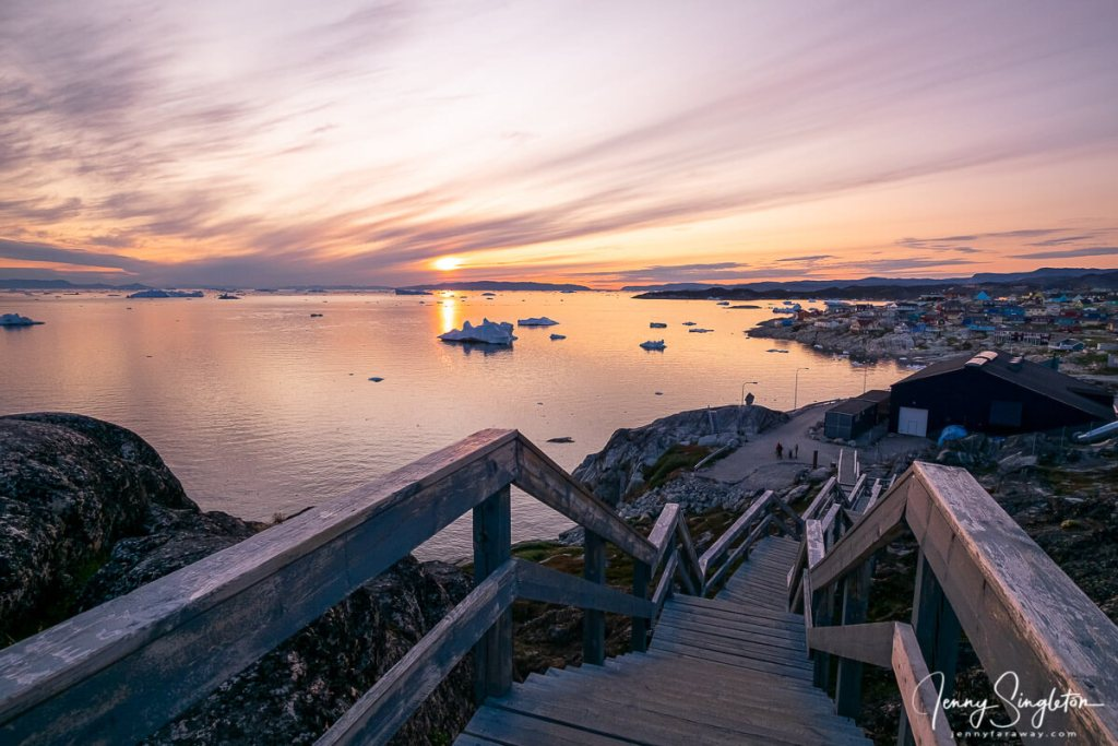 A staircase marks the end (or beginning) of the Yellow Trail in Ilulissat, as the sun hovers on the horizon and creates a pink sunset glow.