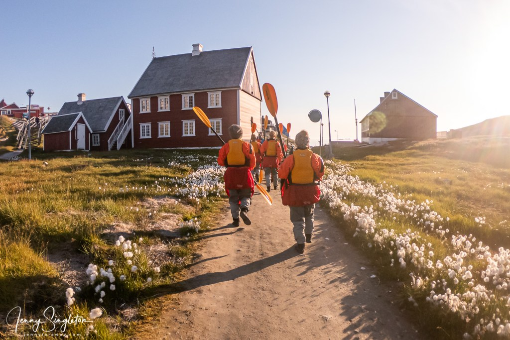Our kayak groups walks down to the waterfront, all dressed in drysuits and carrying paddles, between green lawns and fluffy flowers.
