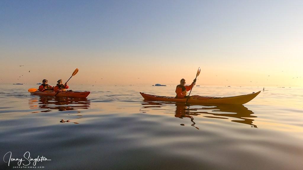 Two kayaks move through still water reflecting the midnight sun.