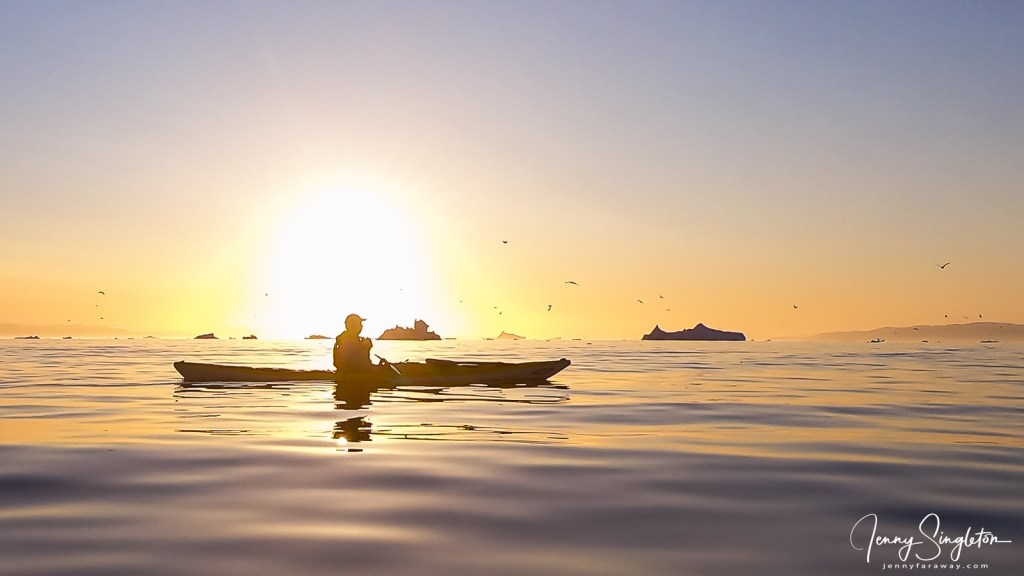 My guide is silhouetted in his kayak by the setting sun in Ilulissat, Greenland