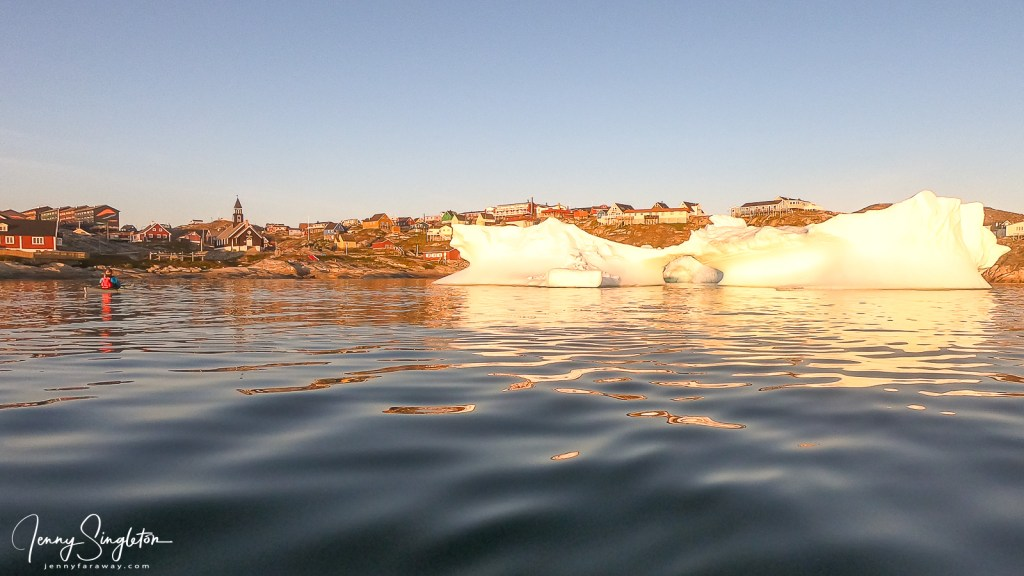 An iceberg sits in front of the town of Ilulissat, taken from low in the water on a kayak.