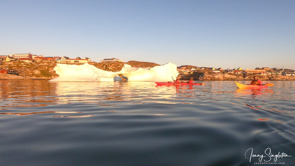 A kayak in front of a big iceberg in Ilulissat, Greenland