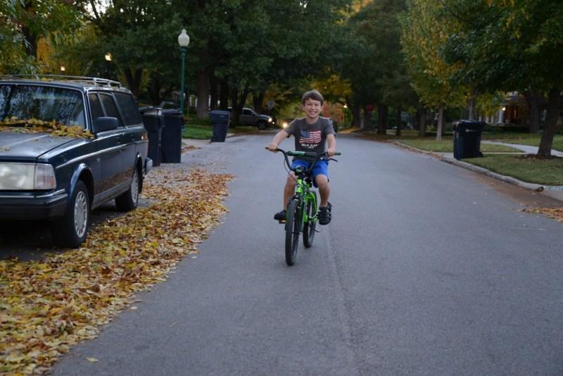 Boy Riding Bike Down Middle of Street