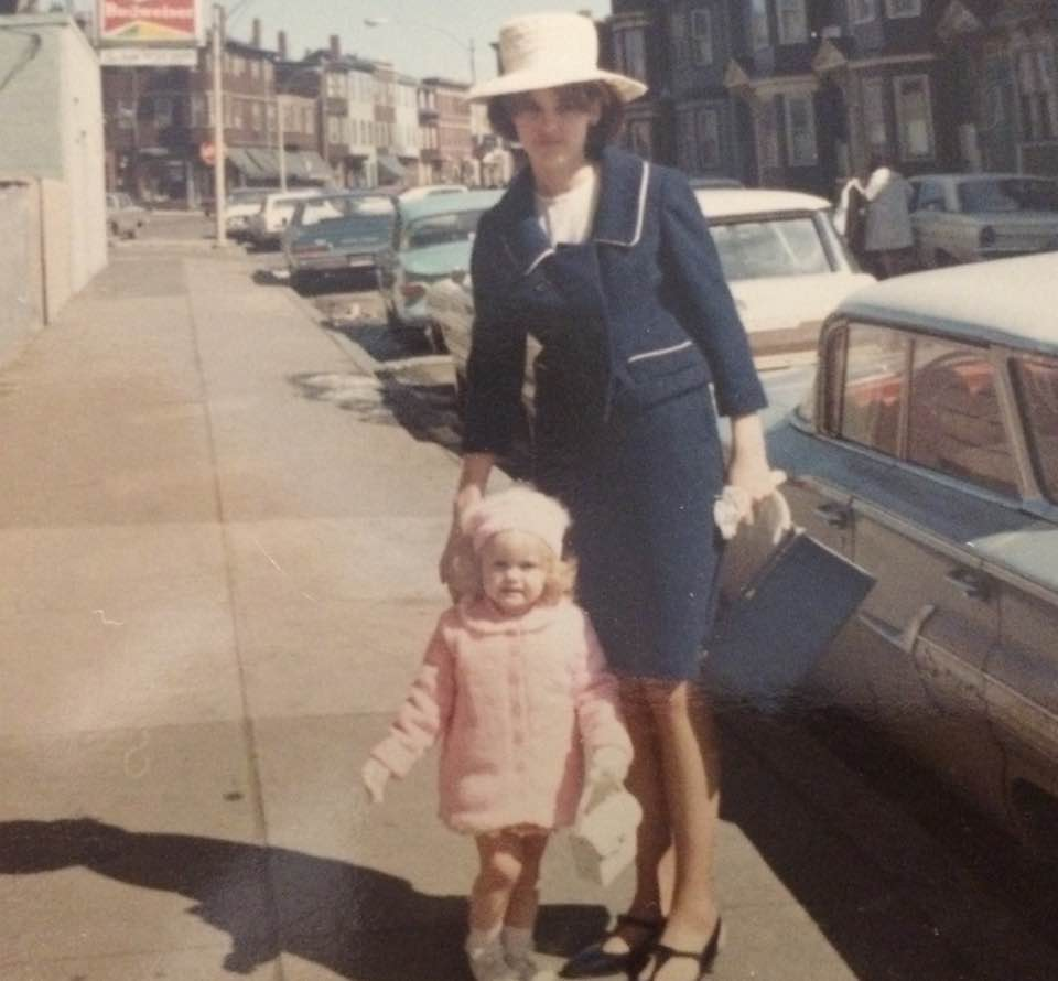 Gorgeous mother in a navy blue suit and matching navy handbag and T-strap shoes poses with her little girl who is dressed all in pink. Easter Sunday, 1967