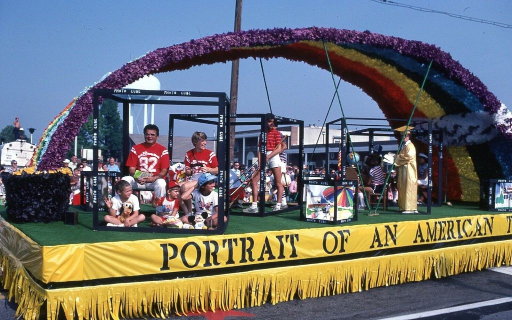 This parade float features a rainbow and people in boxes. They look like they are situated in boxes intended to look like 35mm slides. I'm not sure. The float, like any others in this parade, features the title theme, Portrait of an American Town.
