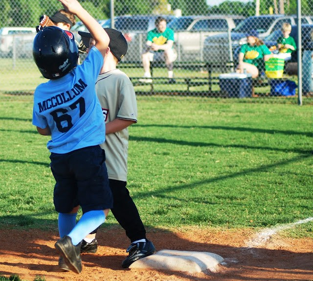Little boy touches first base