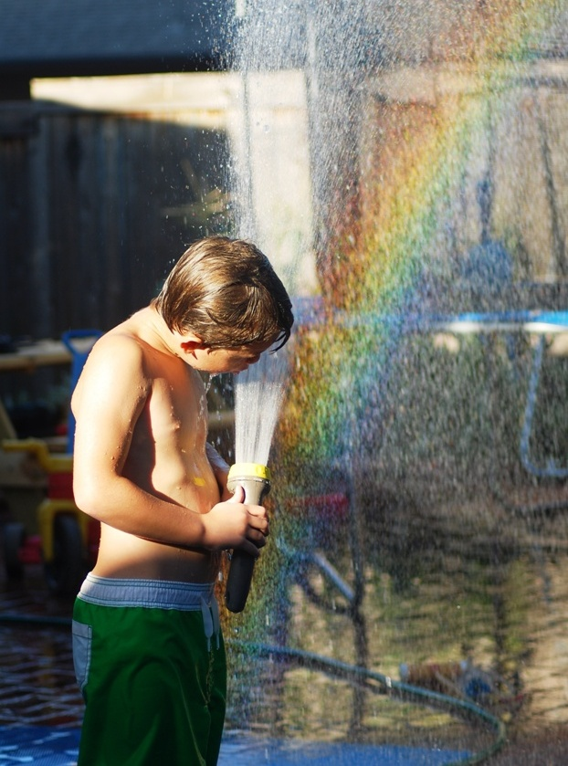 A boy sprays a water hose in the sky opposite the sun and makes a rainbow