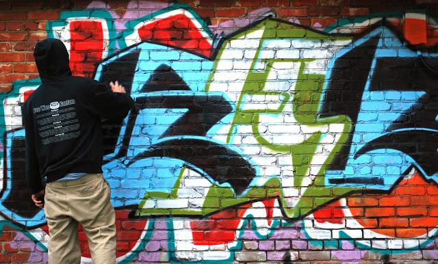 Man spray-painting graffiti in a graffit permission zone.