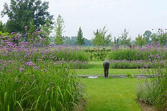 gazon met kleurrijke plantborders vijver en kunst