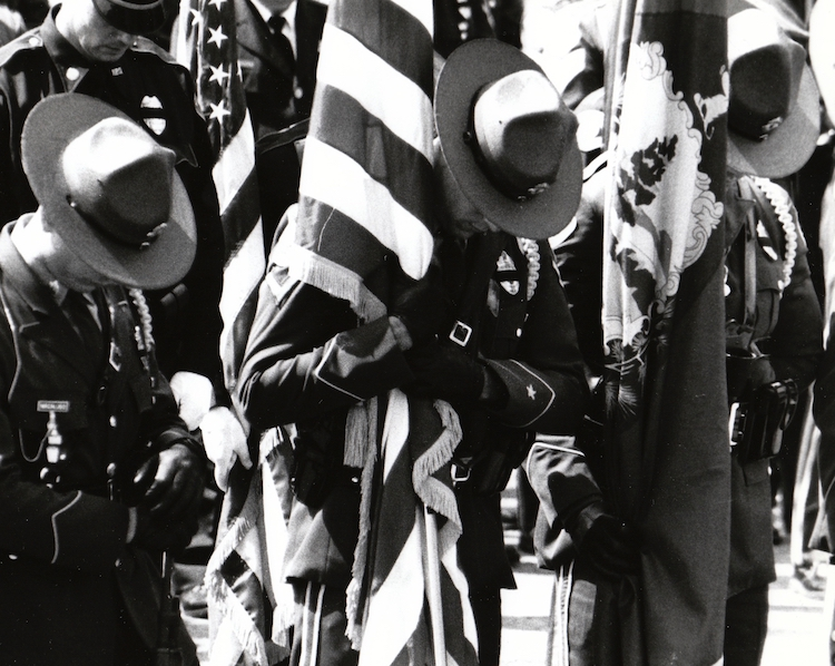 Officers hang their heads as a fallen comrade is put to rest after being killed in action – from Jeremy Larochelle's photo portfolio.