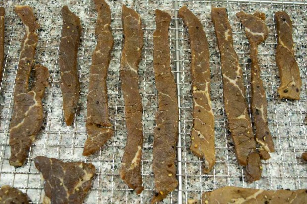 Lemon pepper jerky on dehydrator trays ready to dry