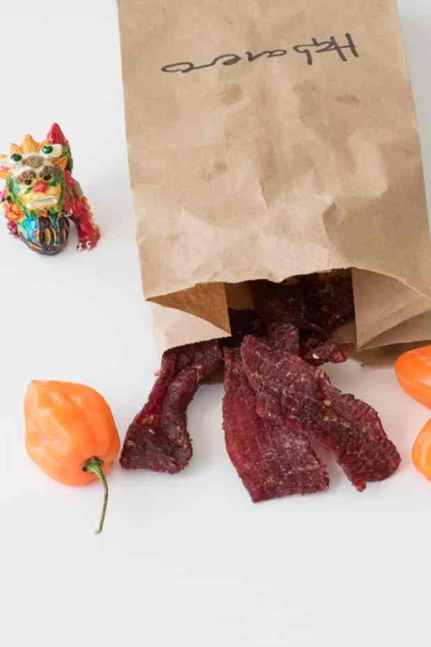 Habanero beef jerky in a paper bag with habaneros around bag