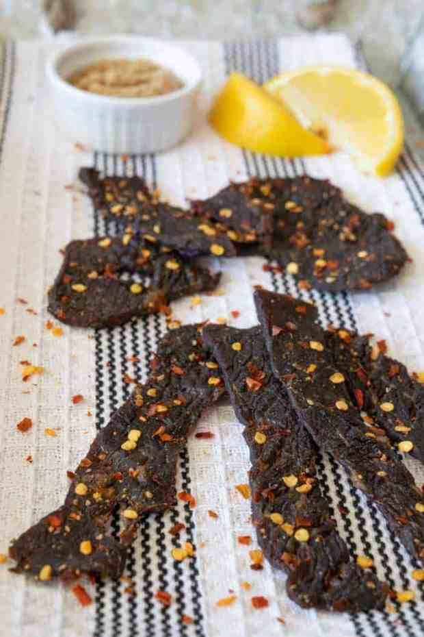 Spicy Sweet beef jerky finished on a towel with lemons and brown sugar